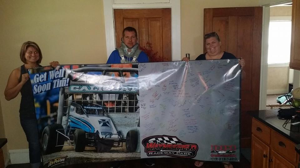 Tim Calicoat hold signed banner